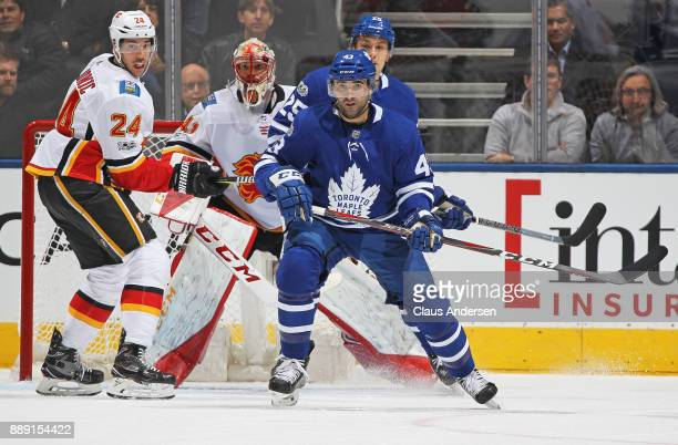 Travis Hamonic of the Calgary Flames skates against Nazem Kadri of the Toronto Maple Leafs during an NHL game at the Air Canada Centre on December 6...