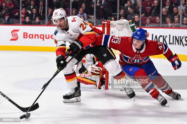 Travis Hamonic of the Calgary Flames skates the puck against Daniel Carr of the Montreal Canadiens during the NHL game at the Bell Centre on December...