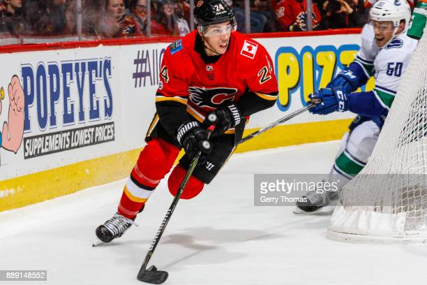 Travis Hamonic of the Calgary Flames skates with the puck in a NHL game against the Vancouver Canucks at the Scotiabank Saddledome on December 09...