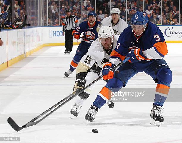 Travis Hamonic of the New York Islanders battles for the puck against Pascal Dupuis of the Pittsburgh Penguins in Game Four of the Eastern Conference...