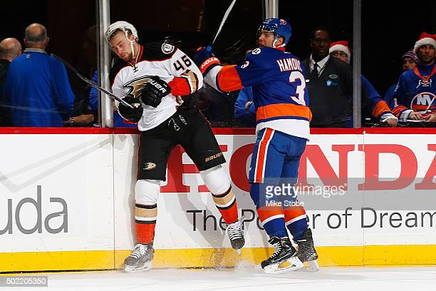 Travis Hamonic of the New York Islanders checks Jiri Sekac of the Anaheim Ducks into the boards at the Barclays Center on December 21 2015 in...