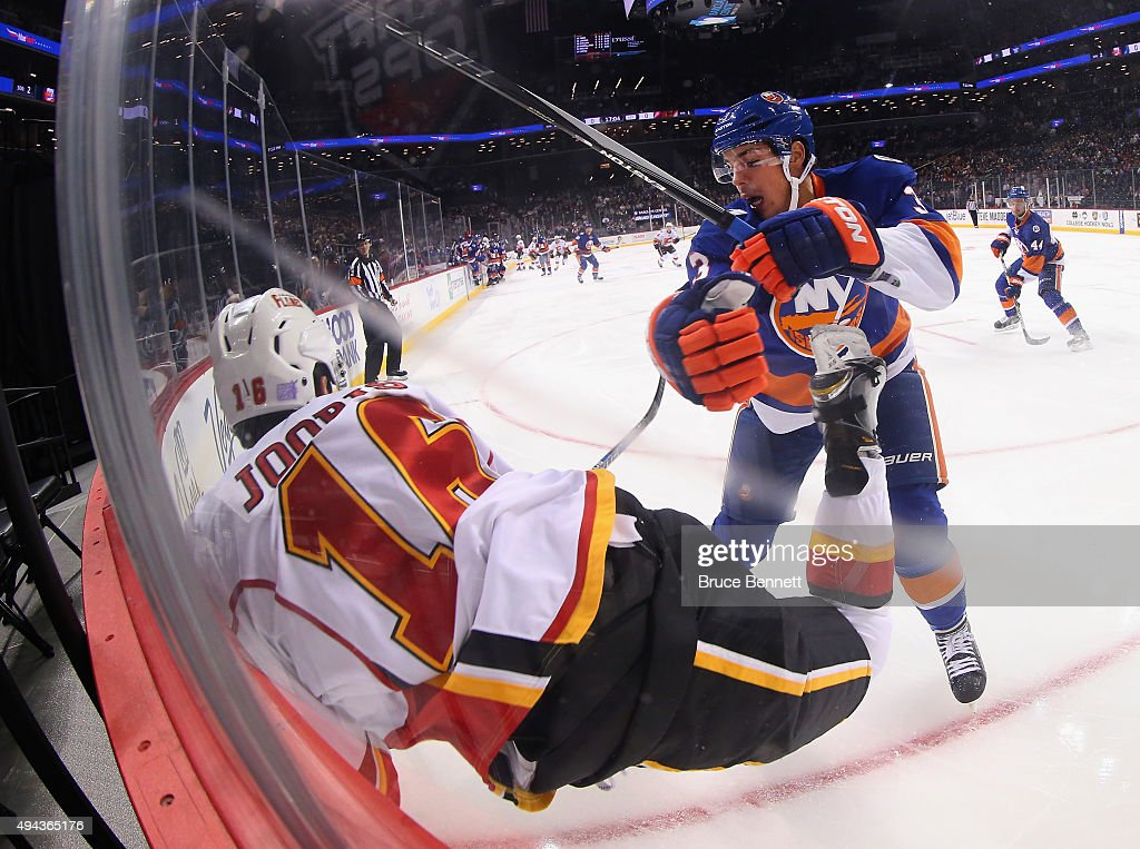 Travis Hamonic #3 of the New York Islanders checks Josh Jooris #16 of the Calgary Flames into the boards during the first period at the Barclays Center on October 26, 2015 in the Brooklyn borough of New York City.