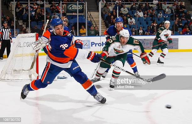 Travis Hamonic of the New York Islanders clears the puck as he's being pursued by Andrew Brunette of the Minnesota Wild on March 2 2011 at Nassau...