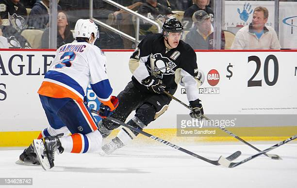 Travis Hamonic of the New York Islanders defends against Evgeni Malkin of the Pittsburgh Penguins during their NHL game at Consol Energy Center on...