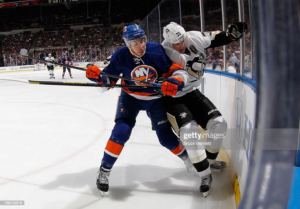 Travis Hamonic #3 of the New York Islanders hits Sidney Crosby #87 of the Pittsburgh Penguins into the boards in Game Three of the Eastern Conference Quarterfinals during the 2013 NHL Stanley Cup Playoffs at the Nassau Veterans Memorial Coliseum on May 5, 2013 in Uniondale, New York.