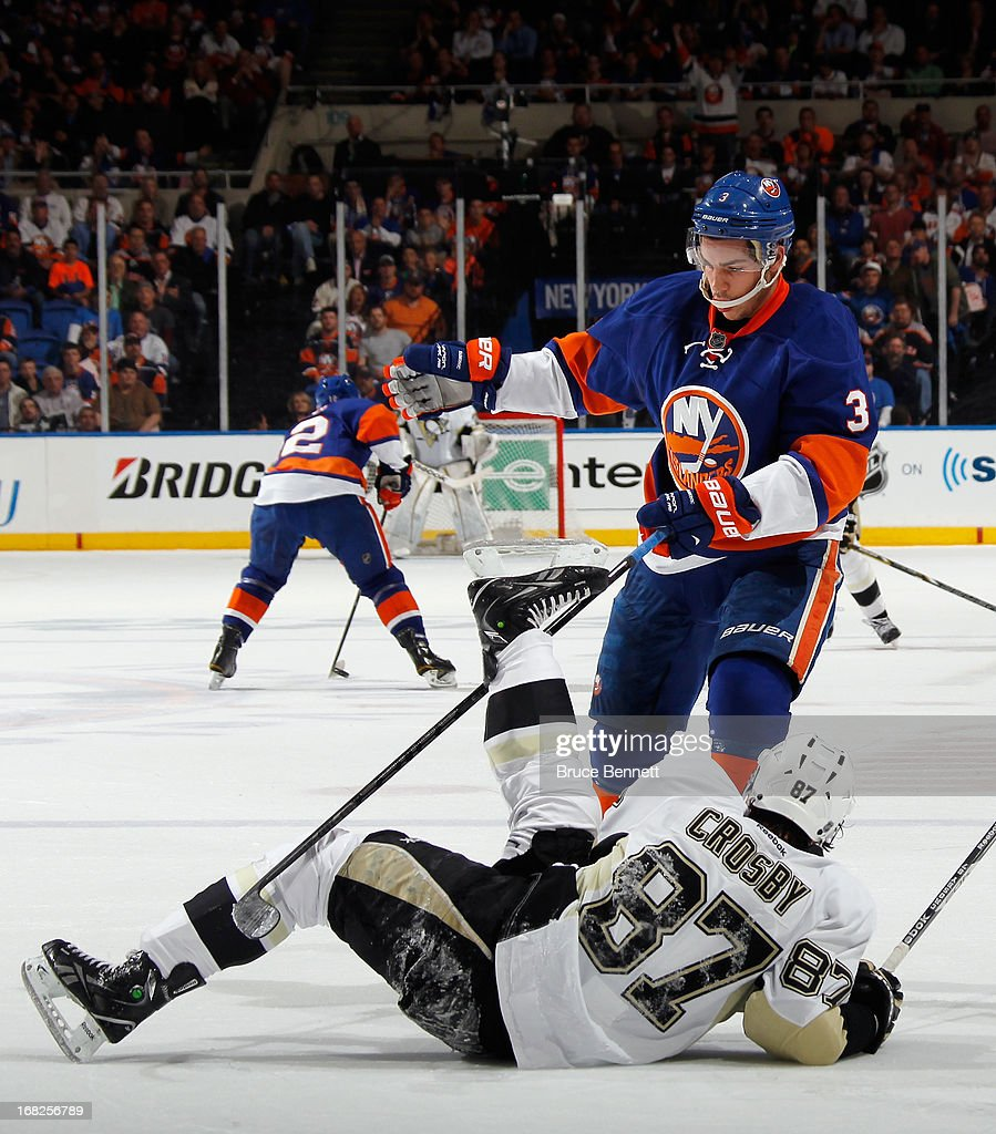 Travis Hamonic #3 of the New York Islanders hits Sidney Crosby #87 of the Pittsburgh Penguins during the first period in Game Four of the Eastern Conference Quarterfinals during the 2013 NHL Stanley Cup Playoffs at the Nassau Veterans Memorial Coliseum on May 7, 2013 in Uniondale, New York.