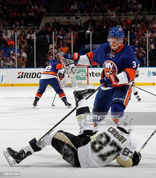 Travis Hamonic of the New York Islanders hits Sidney Crosby of the Pittsburgh Penguins during the first period in Game Four of the Eastern Conference...