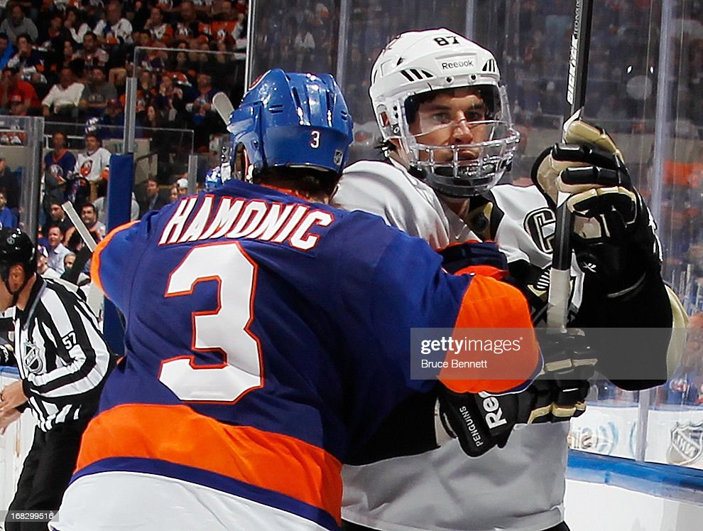 Travis Hamonic #3 of the New York Islanders hits Sidney Crosby #87 of the Pittsburgh Penguins into the boards in Game Four of the Eastern Conference Quarterfinals during the 2013 NHL Stanley Cup Playoffs at the Nassau Veterans Memorial Coliseum on May 7, 2013 in Uniondale, New York. The Islanders defeated the Penguins 6-4.