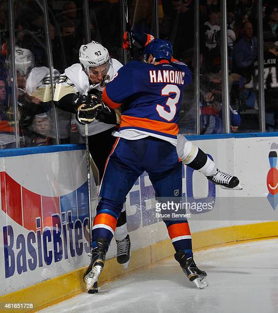 Travis Hamonic of the New York Islanders hits Sidney Crosby of the Pittsburgh Penguins into the boards during the third period at the Nassau Veterans...