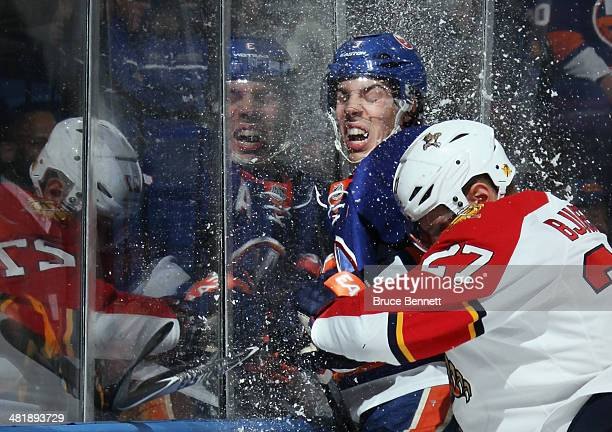 Travis Hamonic of the New York Islanders is hit into the glass by Nick Bjugstad of the Florida Panthers during the first period at the Nassau...