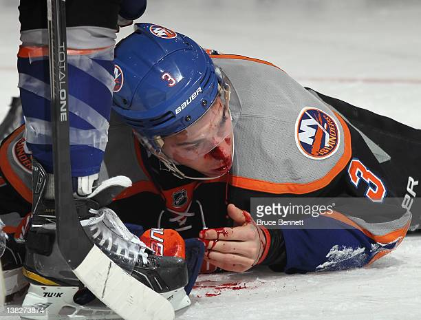 Travis Hamonic of the New York Islanders is hit with a puck in the third period against the Buffalo Sabres at the Nassau Veterans Memorial Coliseum...