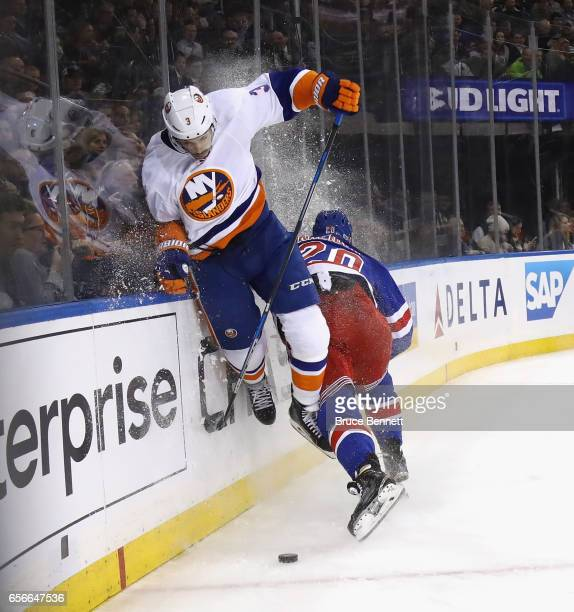 Travis Hamonic of the New York Islanders jumps to avoid a hit from Chris Kreider of the New York Rangers during the second period at Madison Square...