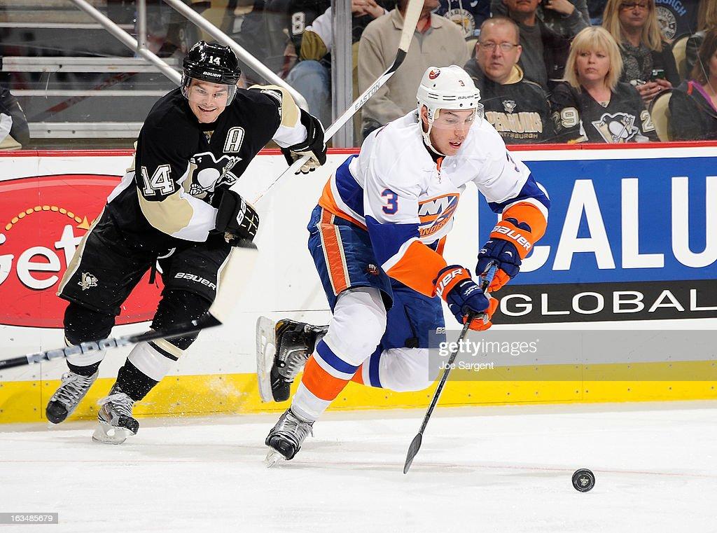 Travis Hamonic #3 of the New York Islanders moves the puck up ice in front of Chris Kunitz #14 of the Pittsburgh Penguins on March 10, 2013 at Consol Energy Center in Pittsburgh, Pennsylvania. Pittsburgh won the game 6-1.