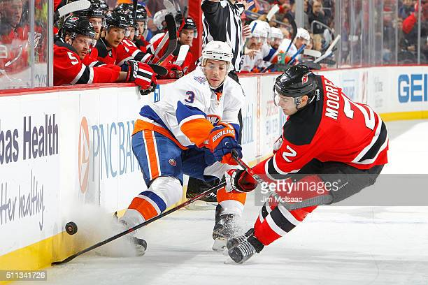 Travis Hamonic of the New York Islanders plays the puxk in the first period against John Moore of the New Jersey Devils at the Prudential Center on...