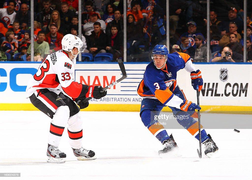 Travis Hamonic #3 of the New York Islanders skates against Jakob Silfverberg #33 of the Ottawa Senators during their game at Nassau Veterans Memorial Coliseum on March 3, 2013 in Uniondale, New York.