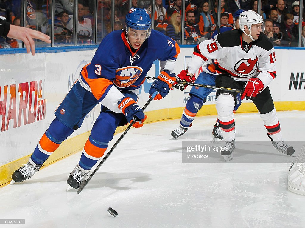 Travis Hamonic #3 of the New York Islanders skates with the puck in front of Travis Zajac #19 of the New Jersey Devils at Nassau Veterans Memorial Coliseum on February 16, 2013 in Uniondale, New York. The Islanders defeated the Devils 5-1.