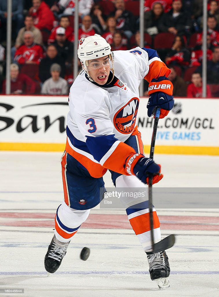 Travis Hamonic #3 of the New York Islanders takes a shot in the third period against the New Jersey Devils at the Prudential Center on January 31, 2013 in Newark, New Jersey.The New York Islanders defeated the New Jersey Devils 5-4 in overtime.