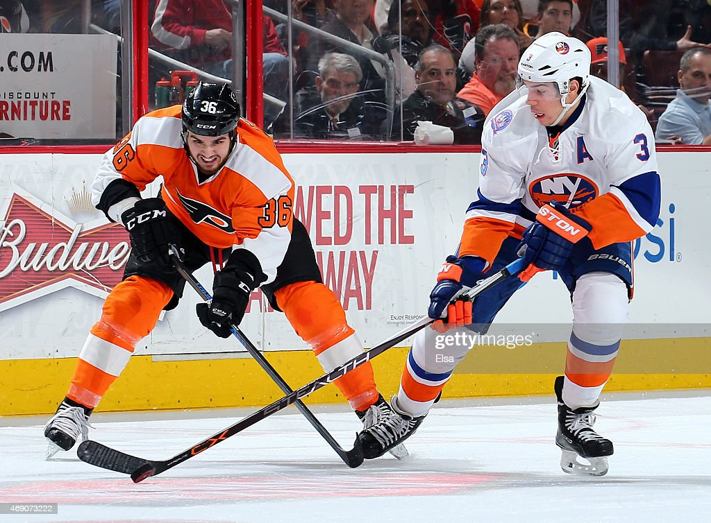 Travis Hamonic #3 of the New York Islanders takes the puck as Zac Rinaldo #36 of the Philadelphia Flyers defends on April 7, 2015 at the Wells Fargo Center in Philadelphia, Pennsylvania.The Philadelphia Flyers defeated the New York Islanders 5-4.