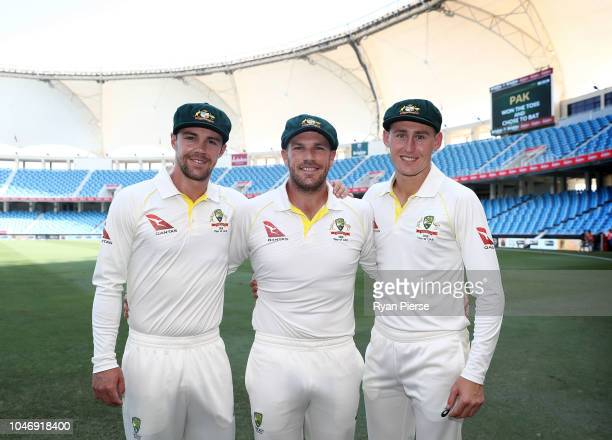 Travis Head Aaron Finch and Marnus Labuschagne of Australia pose after receiving their Baggy Green Caps during day one of the First Test match in the...