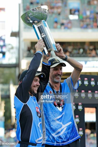 Travis Head and Jason Gillespie coach of the Strikers hold asloft the trophy after winning the Big Bash League Final match between the Adelaide...