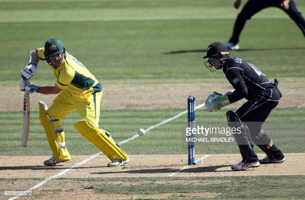 Travis Head of Australia bats watched by New Zealand's Tom Latham during the oneday international cricket match between New Zealand and Australia at...