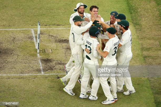 Travis Head of Australia is congratulated after catching Mitchell Santner of New Zealand off a delivery by Pat Cummins of Australia during day four...