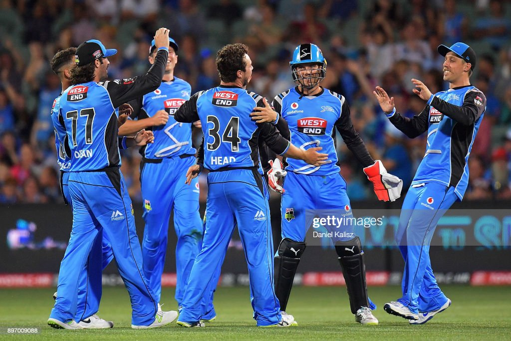 Travis Head of the Adelaide Strikers celebrates with his team mates after taking a wicket during the Big Bash League match between the Adelaide Strikers and the Sydney Thunder at Adelaide Oval on December 22, 2017 in Adelaide, Australia.