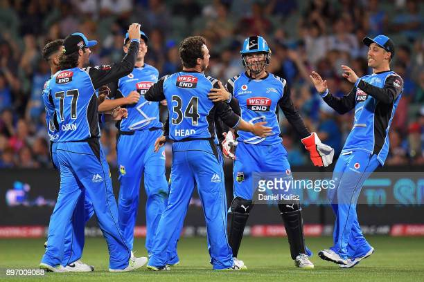 Travis Head of the Adelaide Strikers celebrates with his team mates after taking a wicket during the Big Bash League match between the Adelaide...