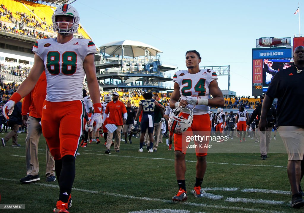 Travis Homer #24 and Brian Polendey #88 of the Miami Hurricanes walk off the field after being upset 24-14 on November 24, 2017 at Heinz Field in Pittsburgh, Pennsylvania.