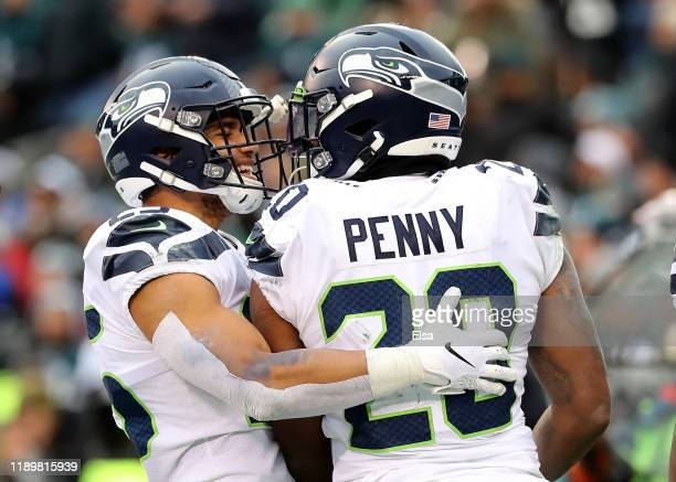 Travis Homer of the Seattle Seahawks congratulates teammate Rashaad Penny after Penny scored in the fourth quarter against the Philadelphia Eagles at...