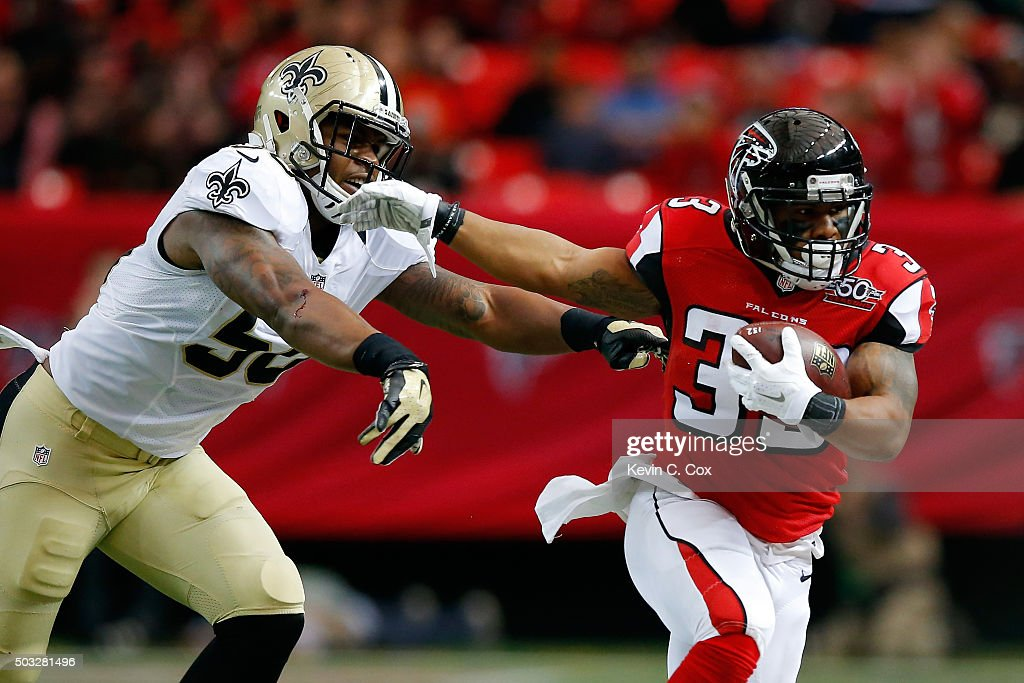 Travis Howard #33 of the Atlanta Falcons breaks away from a tackle by Stephone Anthony #50 of the New Orleans Saints during the first half at the Georgia Dome on January 3, 2016 in Atlanta, Georgia.