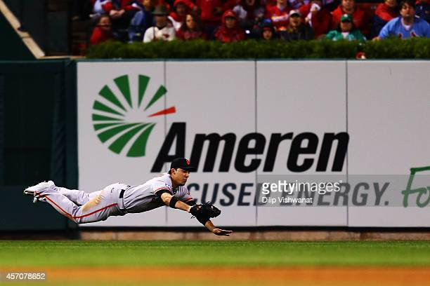 Travis Ishikawa of the San Francisco Giants fields a ball hit by Yadier Molina of the St. Louis Cardinals for an out in the fourth inning during Game...