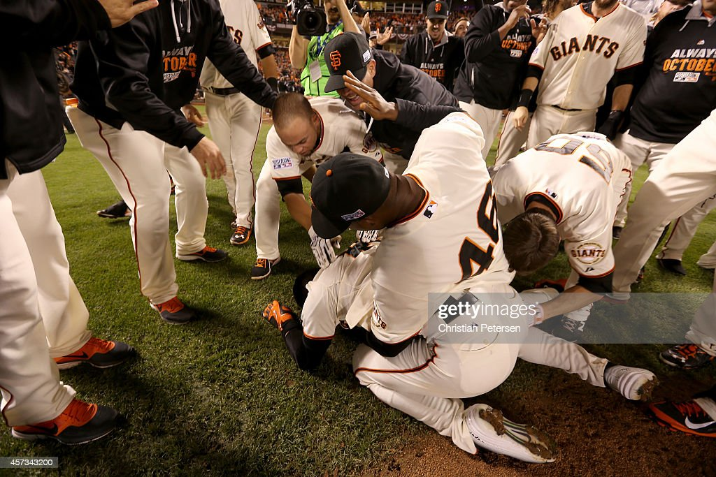 Travis Ishikawa #45 of the San Francisco Giants is on the ground as he celebrates with his teammates after he hits a three-run walk-off home run to defeat the St. Louis Cardinals 6-3 during Game Five of the National League Championship Series at AT&T Park on October 16, 2014 in San Francisco, California.