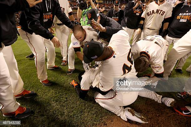 Travis Ishikawa of the San Francisco Giants is on the ground as he celebrates with his teammates after he hits a threerun walkoff home run to defeat...