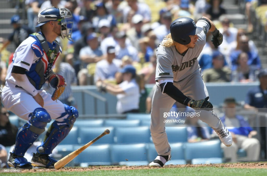 Travis Jankowski #16 of the San Diego Padres drops his bat in front of Yasmani Grandal #9 of the Los Angeles Dodgers as he hits a double in the third inning at Dodger Stadium on May 27, 2018 in Los Angeles, California.