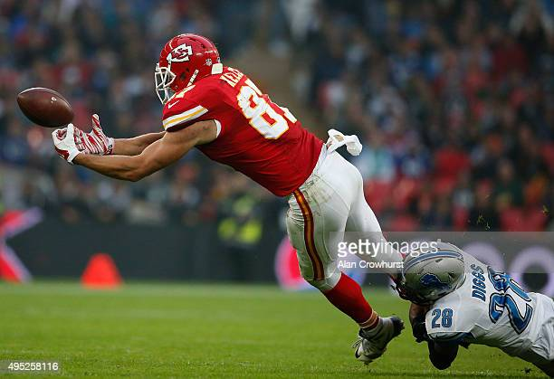 Travis Kelce of Kansas City Chiefs drops a pass as he is tackled by Quandre Diggs during the NFL game between Kansas City Chiefs and Detroit Lions at...