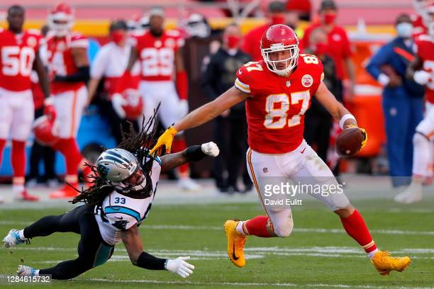 Travis Kelce of the Kansas City Chiefs carries the ball after making an reception against Tre Boston of the Carolina Panthers in the third quarter at...
