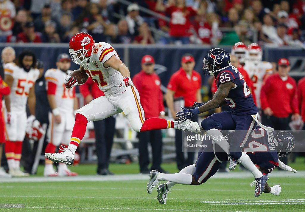 Travis Kelce #87 of the Kansas City Chiefs carries the ball against Kareem Jackson #25 and Johnathan Joseph #24 of the Houston Texans in the fourth quarter during the AFC Wild Card Playoff game at NRG Stadium on January 9, 2016 in Houston, Texas. The Kansas City Chiefs won 30-0.
