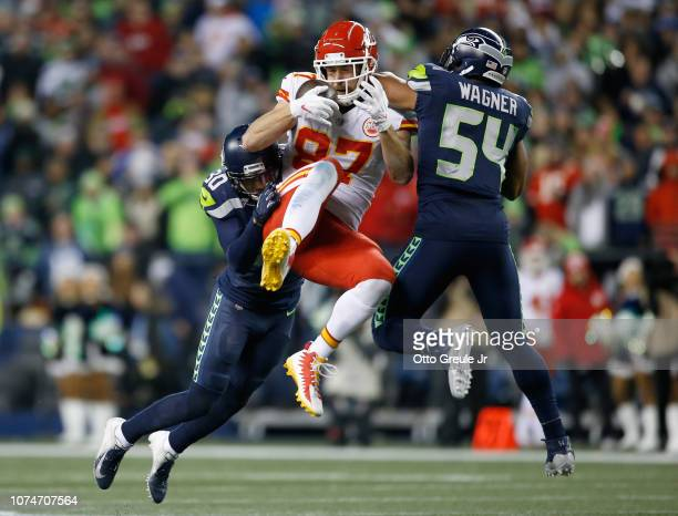 Travis Kelce of the Kansas City Chiefs catches a pass for 23 yards between Bradley McDougald and Bobby Wagner of the Seattle Seahawks during the...