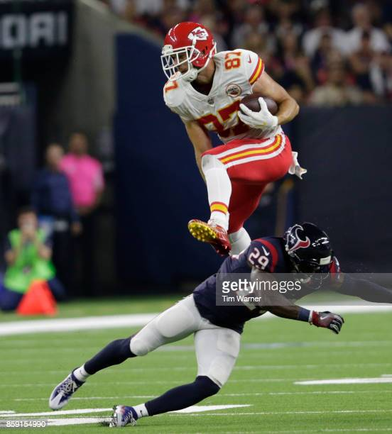 Travis Kelce of the Kansas City Chiefs hurdles Andre Hal of the Houston Texans in the second quarter at NRG Stadium on October 8 2017 in Houston Texas