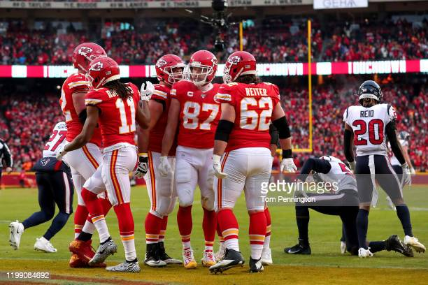 Travis Kelce of the Kansas City Chiefs is congratulated by his teammates Eric Fisher after his third touchdown reception of the second quarter...