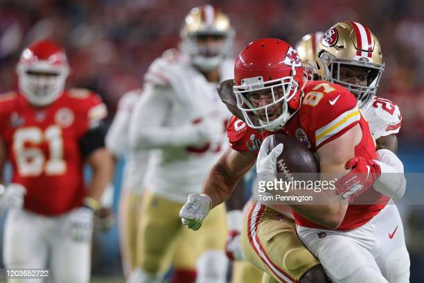 Travis Kelce of the Kansas City Chiefs is tackled by Jimmie Ward of the San Francisco 49ers during the first quarter in Super Bowl LIV at Hard Rock...
