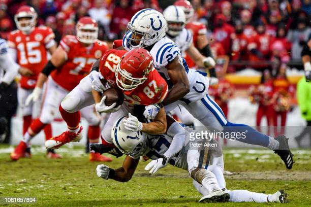 Travis Kelce of the Kansas City Chiefs is tackled by JJ Wilcox and teammate Kenny Moore of the Indianapolis Colts during the first quarter of the AFC...