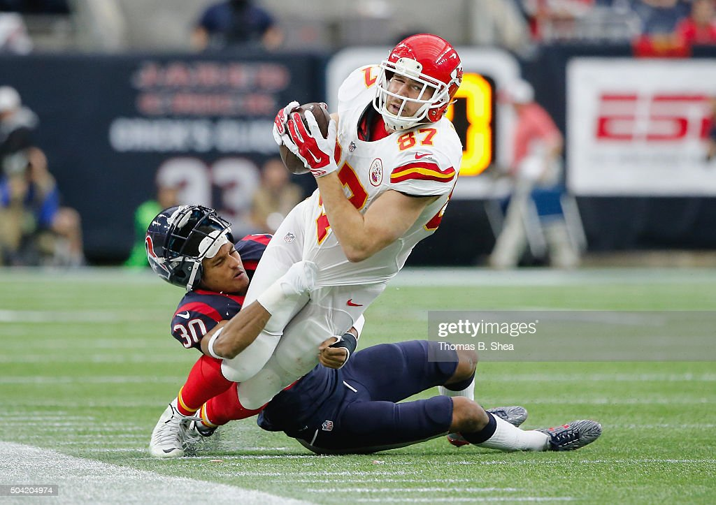 Travis Kelce #87 of the Kansas City Chiefs is tackled by Kevin Johnson #30 of the Houston Texans in the second quarter during the AFC Wild Card Playoff game at NRG Stadium on January 9, 2016 in Houston, Texas.