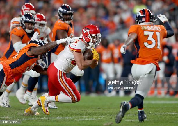 Travis Kelce of the Kansas City Chiefs is tackled by the defense of the Denver Broncos in the game at Broncos Stadium at Mile High on October 17 2019...