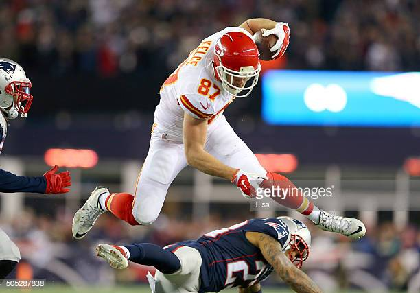 Travis Kelce of the Kansas City Chiefs jumps over Patrick Chung of the New England Patriots in the first half during the AFC Divisional Playoff Game...