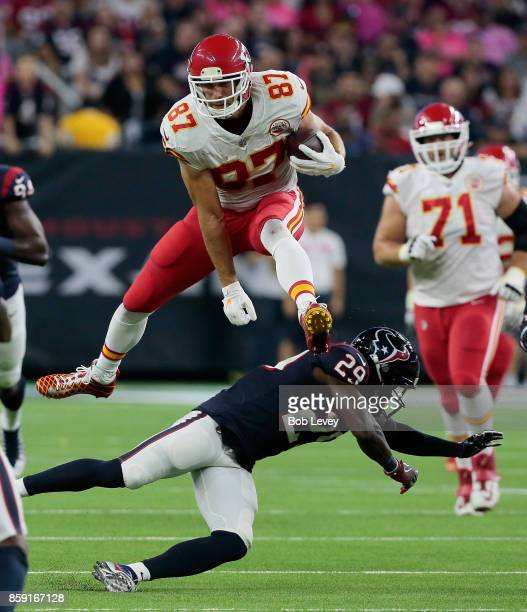 Travis Kelce of the Kansas City Chiefs leaps over Andre Hal of the Houston Texans as he runs with the ball after a catch in the first half at NRG...