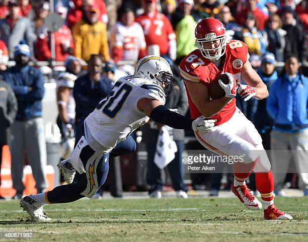 Travis Kelce of the Kansas City Chiefs runs the ball against Manti Te'o of the San Diego Chargers during the first quarter at Arrowhead Stadium on...