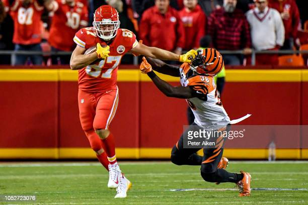 Travis Kelce of the Kansas City Chiefs stiff arms Shawn Williams of the Cincinnati Bengals during the first half of the game at Arrowhead Stadium on...