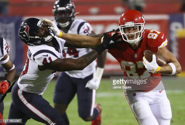 Travis Kelce of the Kansas City Chiefs stiff arms Zach Cunningham of the Houston Texans during the second quarter at Arrowhead Stadium on September...